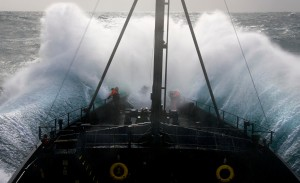Captain Paul Watson, photographer Eric Cheng, and cameraman John Mans brace themselves on the bow of the MY Steve Irwin as it plunges into the trough of a massive wave in rough seas in the Southern Ocean on Jan. 9, 2009. (Photo by Adam Lau/Sea Shepherd Conservation Society)