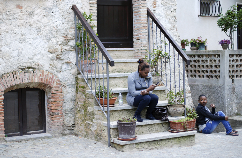 Two women talk as they sit in Riace