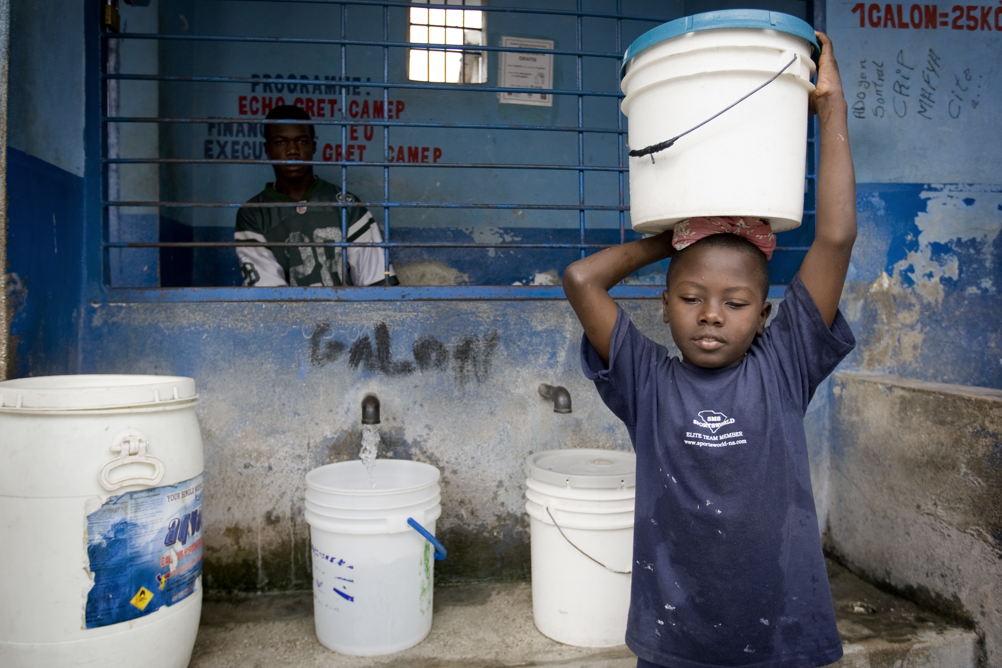 A boy buys water at a distribution point in Cite L'Eternel, a poor neighborhood of Port au Prince. UNICEF, through the NGO Gret, distributes thousands of aqua-tabs to the Haitian population to respond to the cholera outbreak that killed over 1000 people.