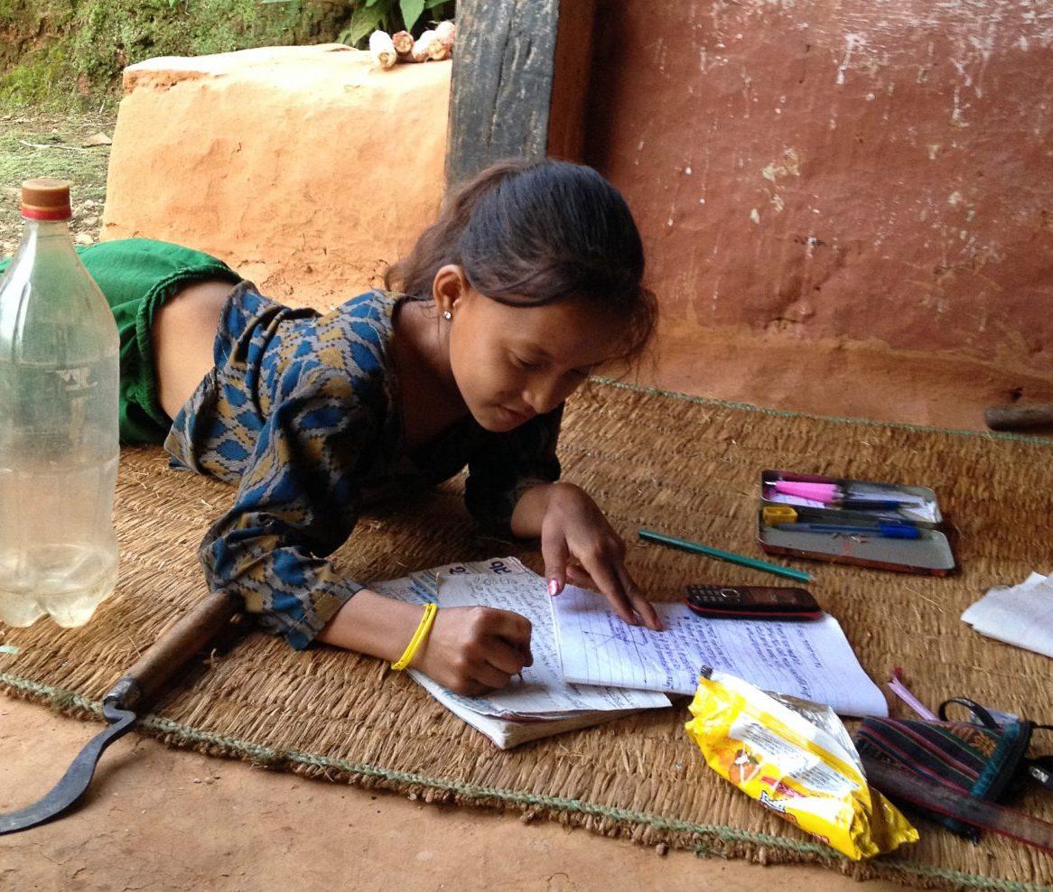 Photo: Anita finishing her English homework before preparing dinner. Photo Credit: Katherine Baxter