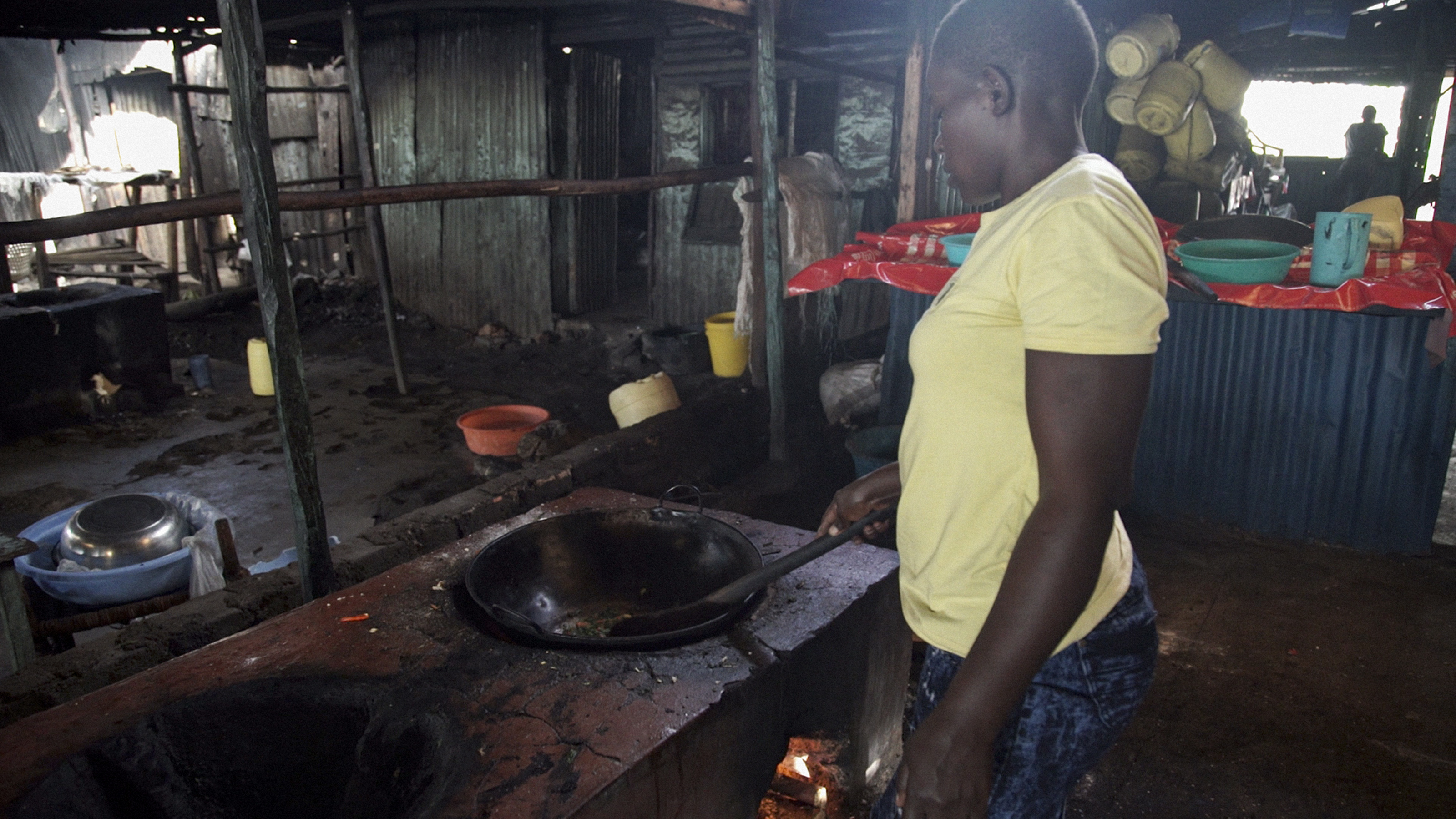 A cook prepares food in her restaurant on a recently installed rocket stove on the shores of Lake Victoria in Kisumu, Kenya. The rocket stoves are cleaner and more effiecient, allowing restaurants to expand and serve more customers. Photo: Petr Kapuscinski / World Bank