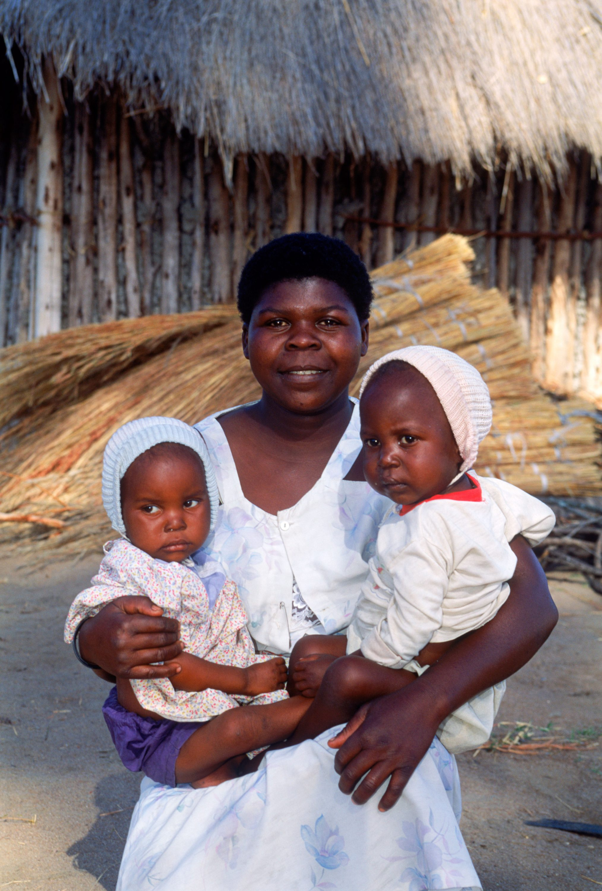 African woman holding two babies in her arms in front of village hut in rural Zimbabwe