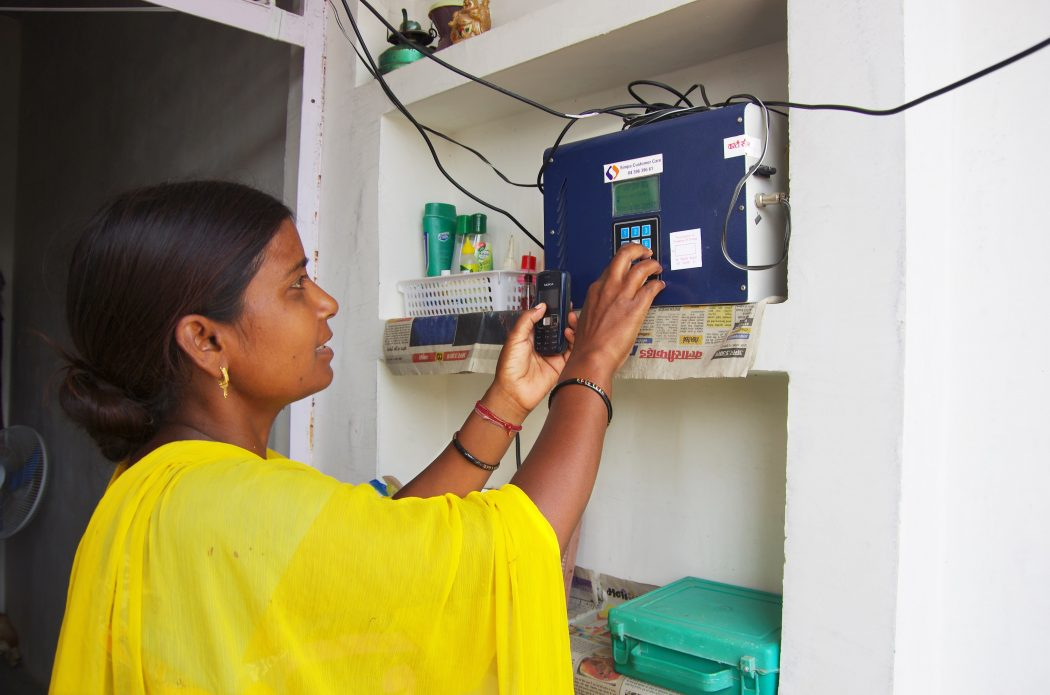 A women recharging her Simpa Pay-Go meter for uninterupted electricity