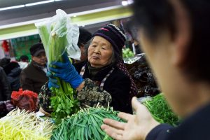 05 March 2016, Beijing, China - Shoppers and vendors handling produce at a local market near Beijing's Lucky Street.