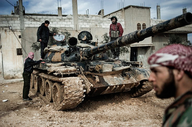 Free Syria Army members pose beside an abandoned tank. The Syrian opposition and Western powers insist that Syrian President Assad steps down from power. Photo courtesy of Freedom House.