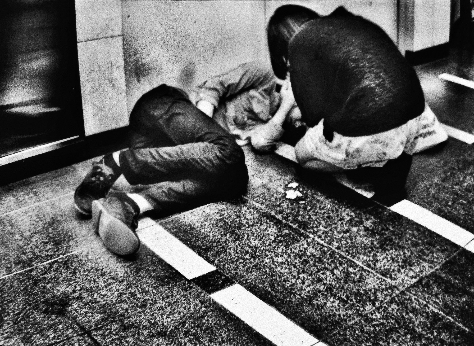 A girl tries to help her heavily drunk boyfriend who collapsed in an alley in Shinjuku. Early evening hard drinking is a widespread habit among the often depressed young generation in Tokyo.